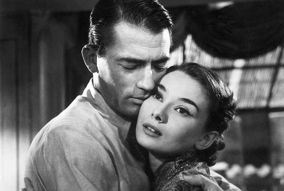 Promotional image of Roman Holiday. Gregory Peck and Audrey Hepburn lean in for an embrace.