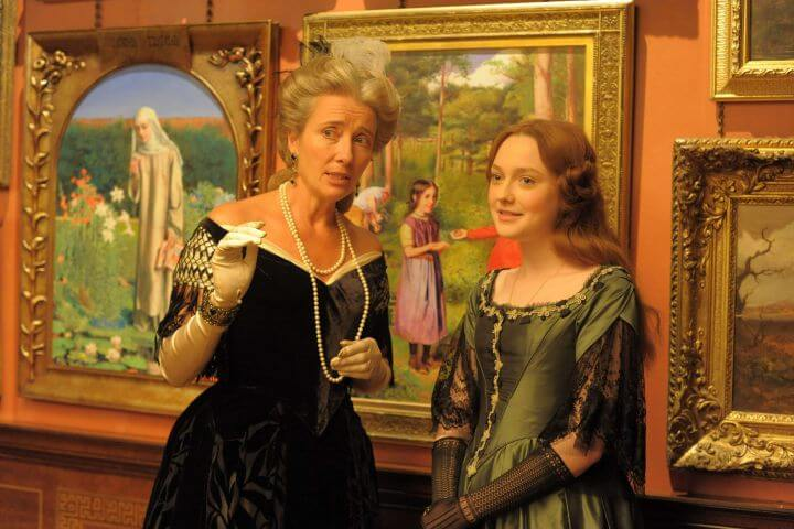 Emma Thompson and Dakota Fanning in Effie Gray publicity photo. Paintings are behind them.