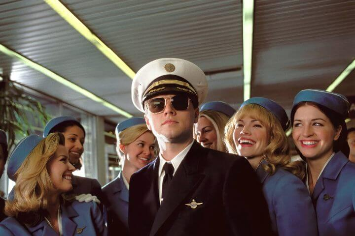 Catch Me If You Can promo photo with Leonardo Dicaprio dressed as a pilot and female flight attendants standing around him.