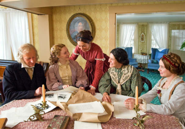 The Alcott family looks over the pages of Little Women in a scene filmed at Orchard House in Concord. Photo Credit: Liane Brandon