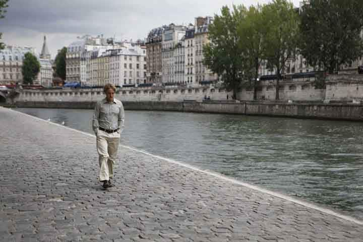 Gil strolling along the river in Midnight in Paris.