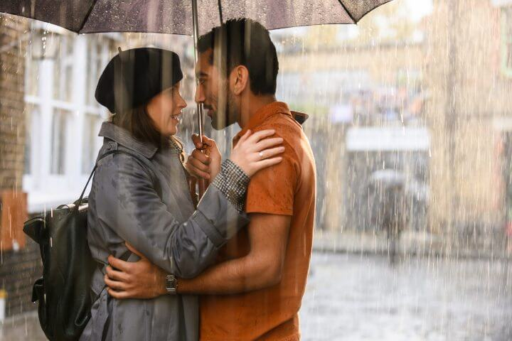 The Last Letter from Your Lover promo photo; couple in the rain with umbrella
